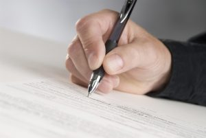 man holding a pen writing his signature